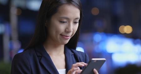 Donna d'affari che usa il cellulare di notte