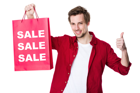Happy man shopping with his thumbs up and showing three sale word