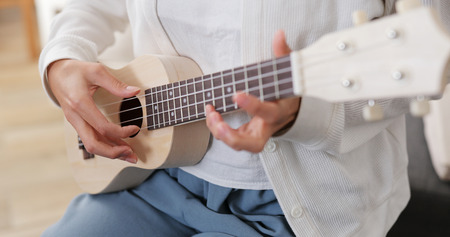 Woman play ukulele at home Standard-Bild