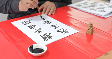 Man pratice chinese calligraphy for lunar new year, words mean wish you a prosperous Year
