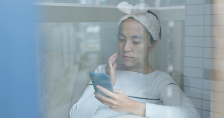 Woman doing facial mask and using mobile phone