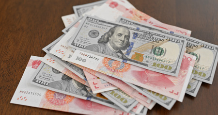 Counting with chinese RMB and USD banknote Stock Photo