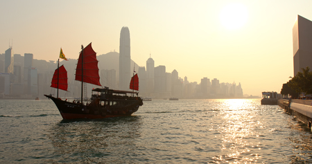 Victoria Harbour, Hong Kong 15 march 2019: Hong Kong Victoria harbor and red sail junk boat in the evening Editorial