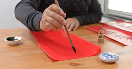 Man write chinese calligraphy for lunar new year