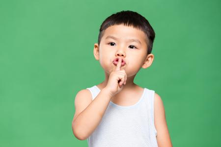 Kleines Kind, das einen Finger auf seine Lippen legt