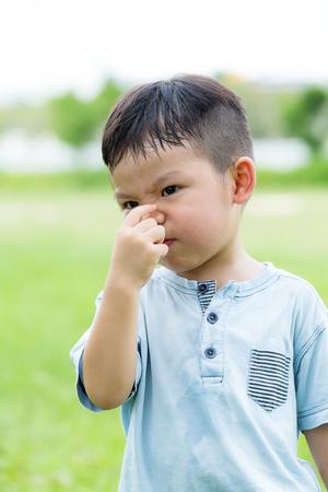 Kleiner Junge mit Handkneife auf der Nase Standard-Bild