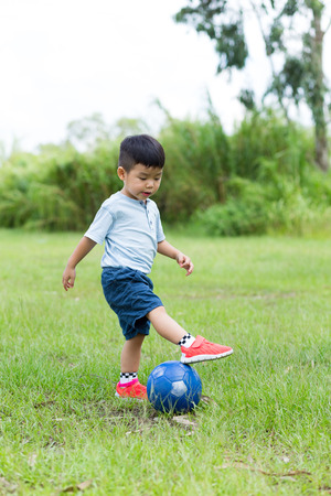 Asian little boy playing soccer ball at park 免版税图像