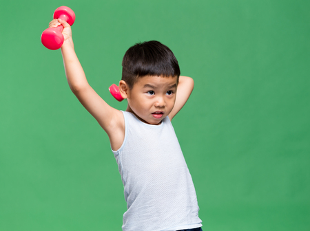 Asiatischer kleiner Junge, der Hanteln hochhebt Standard-Bild