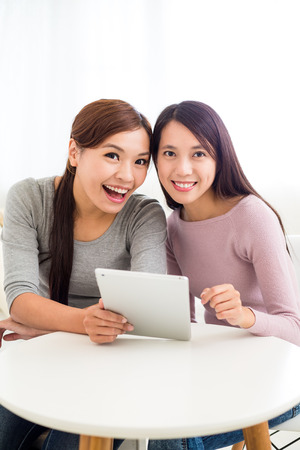 Two girls use of the tablet pc together Imagens