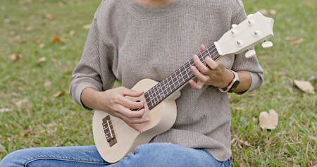 Woman enjoy play ukulele