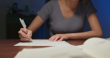 Woman write on the paper at home in the evening