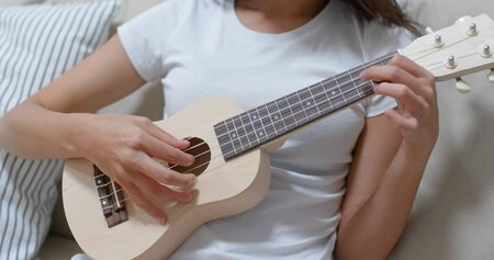 Woman play ukulele at home 版權商用圖片