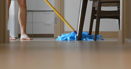 Woman clean the floor at home with mop