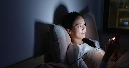 Utilisation d'un téléphone portable par une femme sur le lit la nuit Banque d'images