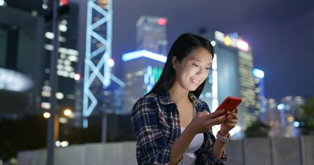 Woman use of cellphone in the city at night