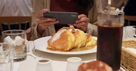 Woman take photo on cellphone with her souffle pancake in coffee shop