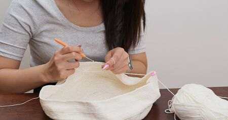 Woman knitter making fabric from thread