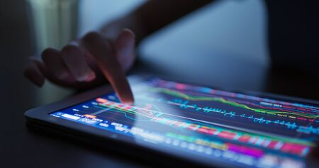 Finger touch on tablet computer with stock market data