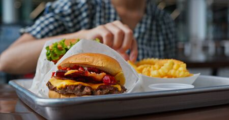 Woman eat burger in fast food restaurant Stock fotó