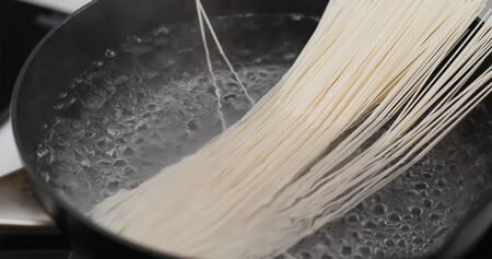 Cooking with noodle in skillet in the kitchen Stock Photo