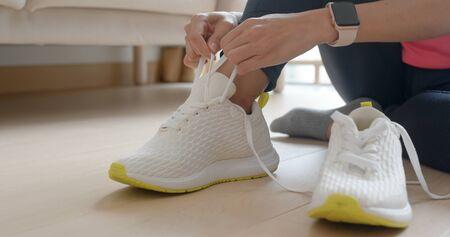Donna che indossa scarpe sportive a casa per correre
