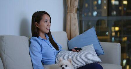 Woman watch tv with her dog at night 版權商用圖片