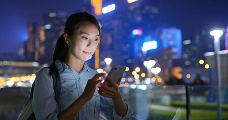 Woman use of mobile phone at city