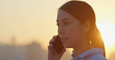 Woman talk to mobile phone in city at sunset