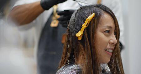 Woman have hair dye at beauty salon