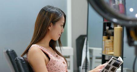 Woman pick a color for hair dye in beauty salon 版權商用圖片