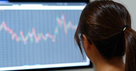 Woman look at the stock market graph at office 版權商用圖片