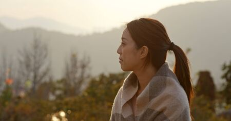 Woman look at the countryside at sunset time