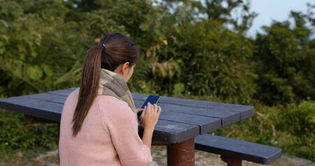 Woman check on mobile phone at countryside