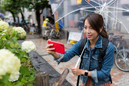 Woman take photo on flower at rain day