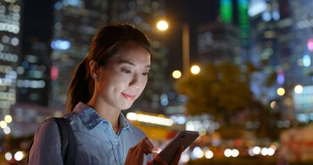 Woman use smart phone at street in evening