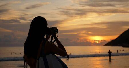 Woman take photo on camera at the sea beach under beautiful sunset