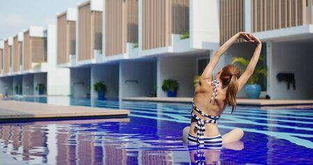 Woman do yoga at swimming pool 免版税图像