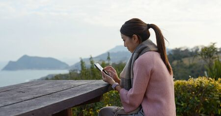 Woman use of mobile phone at countryside