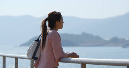 Woman go countryside and look at the sea