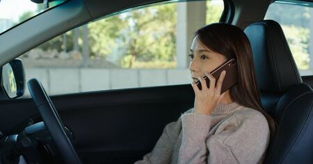 Woman talk to cellphone and drive a car