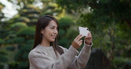 Woman take photo on mobile phone at park 免版税图像