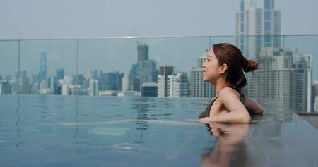 Woman sit at the infinity swimming pool 免版税图像
