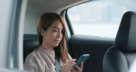 Woman use mobile phone and sits inside car 免版税图像