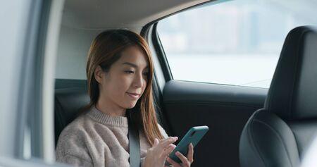 Woman use mobile phone and sits inside car 版權商用圖片