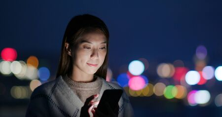Woman look at cellphone in city at night