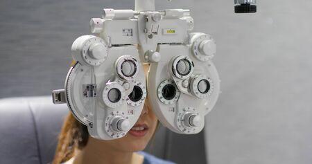 Woman checks her eye in clinic 免版税图像