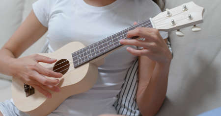 Woman pratice ukulele at home