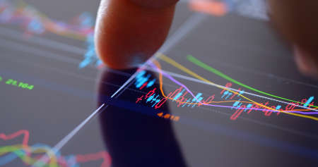 Finger touch on screen with stock market data