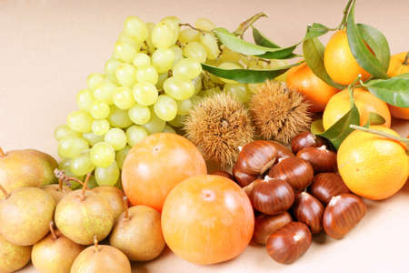 Assortment of autumn fruits over a light brown background