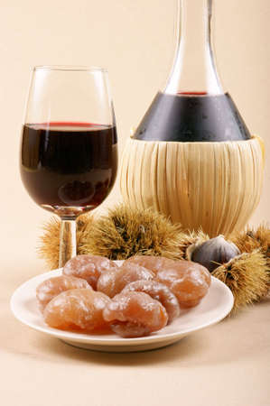Autumn flavours: chestnuts, marron glacé and young wine. Light brown background.